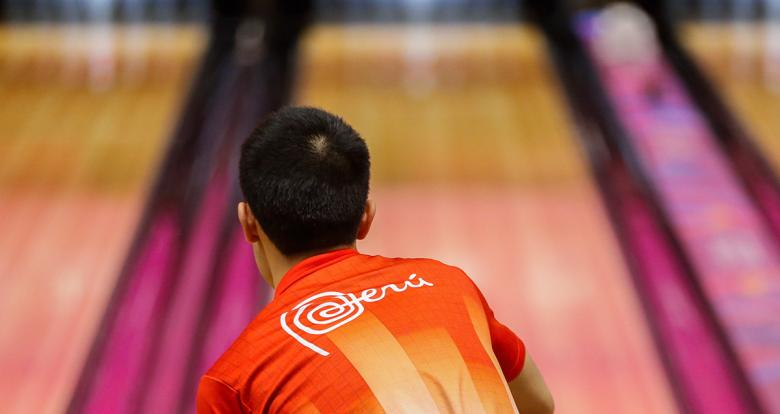 Alejandro Yum, from the Peruvian bowling team, throws a ball during the competition