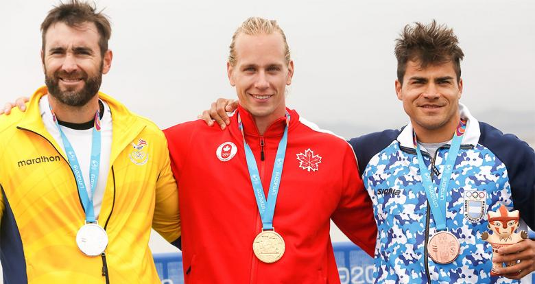 : Canadian Dominik Crete, Ecuadorian César de Cesare, and Argentinian Rubén Rezola smiling while standing at the podium of K1 men 200m event at Lima 2019