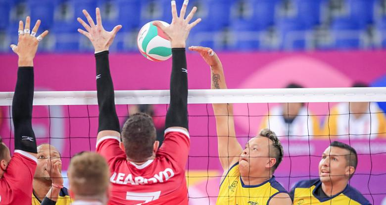 Colombian Carlos Valencia returns the ball to Canadian Douglas Learoyd in Lima 2019 sitting volleyball match held at the Callao Regional Sports Village