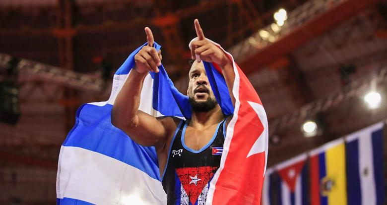 Alejandro Valdes celebrates with the Cuban flag his victory against Dominican Albaro Rudesindo at the Callao Regional Sports Village at Lima 2019