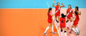 Peruvian national team celebrates scoring a point during a volleyball championship.