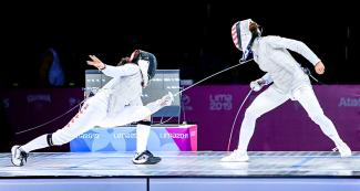 Canadian Jessica Guo and American Lee Kiefer fight a bout during the women's individual foil final at the Lima Convention Center