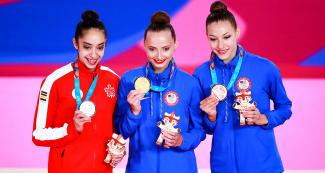 Natalie Garcia, Camilla Feeley, and Evita Griskenas, showing their medals at  Villa El Salvador Sports Center in the Lima 2019 Games