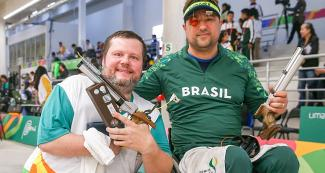 Geraldo Rosenthal and Adriano Sergio from Brazil pose proudly after having won the shooting Para sport 10 m air pistol competition at Lima 2019, in the Las Palmas Airbase