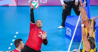 Canadian Jesse Buckingham returns the ball to Colombia in Lima 2019 sitting volleyball match against Canada held at the Callao Regional Sports Village